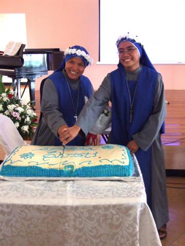 Newly professed sisters cutting cake